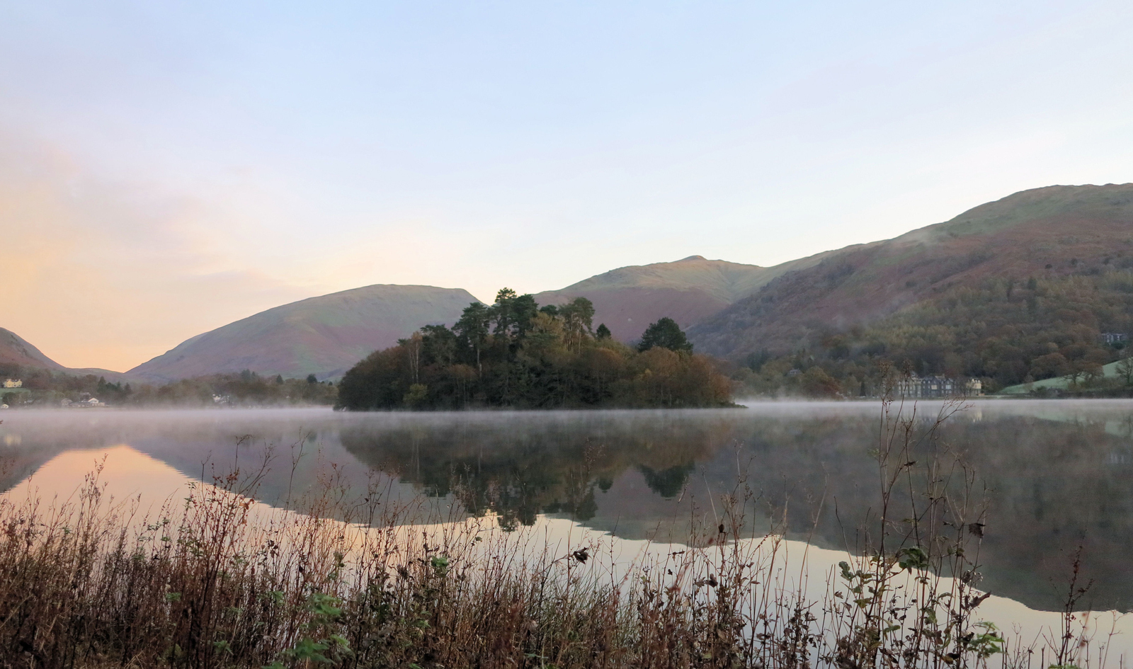 A misty lake in Grasmere surrounded by rolling green hills at dawn