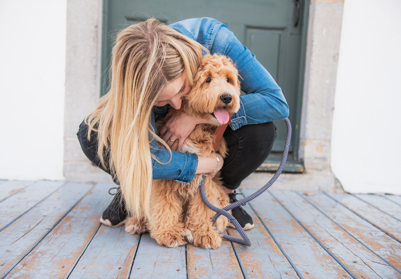 a woman with blonde hair cuddling her cute dog