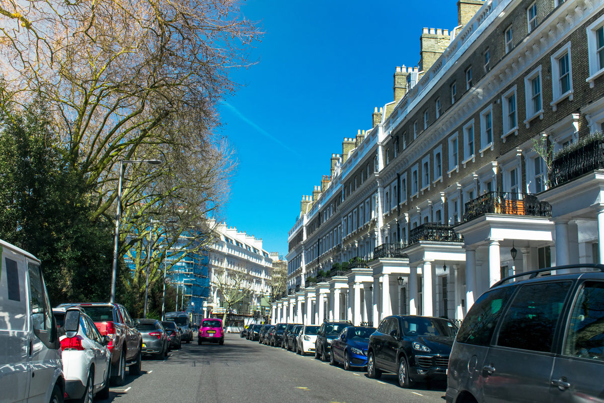 A busy residential road in London with Townhouses lining one side of the road and a park on the other